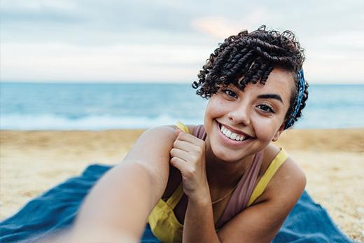 Mujer morena con pelo rizado sonríe mientras se hace un selfie