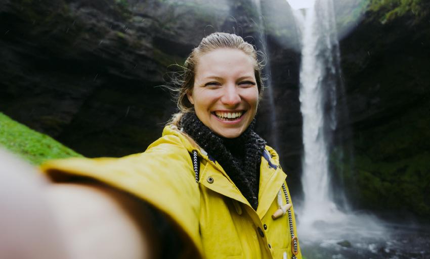 Mujer rubia sonríe, mientras se hace un selfie.