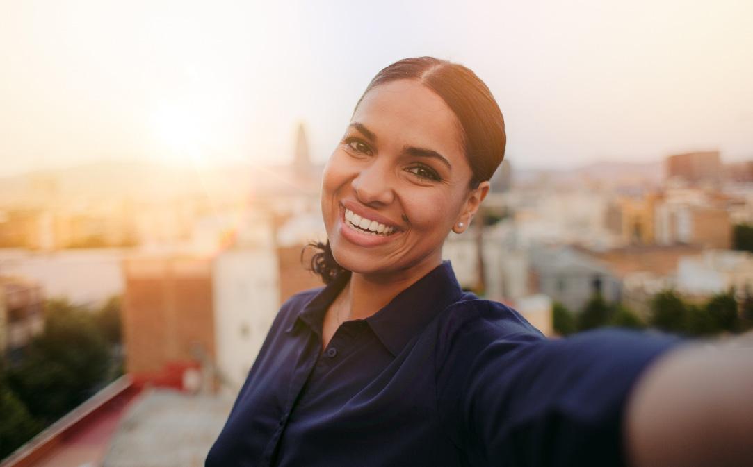 Mujer de piel morena sonríe, mientras se hace un selfie.
