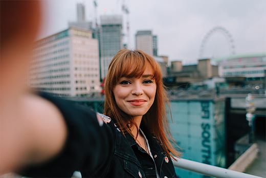 Mujer pelirroja sonríe mientras se hace un selfie
